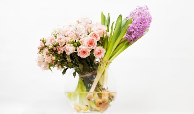 Gros plan de fleurs colorées dans un vase en verre contre blanc