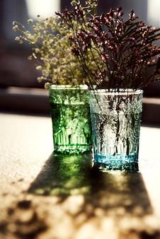 Gros plan de fleurs dans des vases en verre sur une table en bois