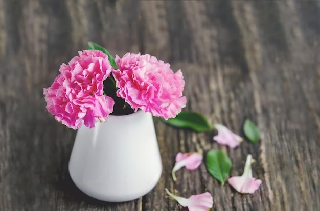 Gros plan des fleurs d'oeillets roses dans un vase blanc sur une table en bois