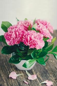 Gros plan de fleurs d'oeillets roses sur une table en bois avec ton vintage