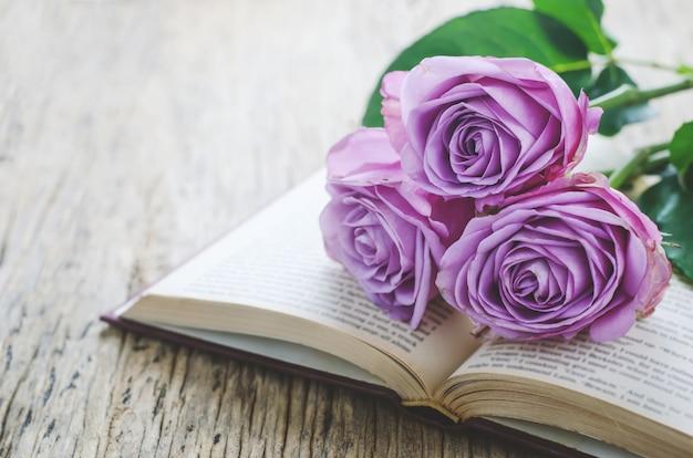 Gros plan de fleurs roses violettes violettes et livre ouvert avec ton vintage