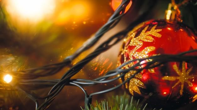 Gros plan flou fond d'arbre de noël décoré de boules et de guirlandes lumineuses à led