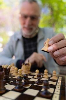 Gros plan flou homme jouant aux échecs