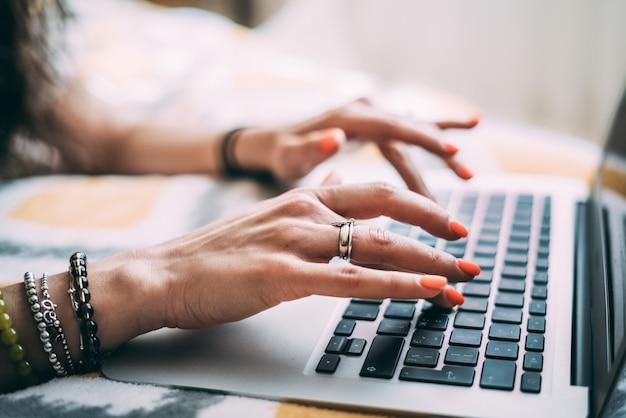 Gros plan flou des mains féminines, avec des accessoires qui se trouvent sur un clavier d'ordinateur portable.