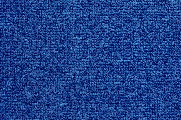 Gros plan de fond de texture de tapis de couleur bleu foncé avec motif sans soudure.