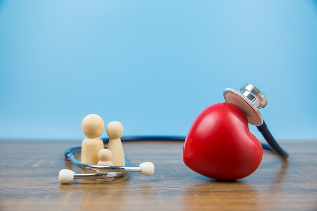 Gros plan d'une forme de coeur rouge et d'un stéthoscope médical en famille.
