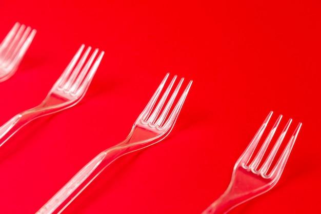 Gros plan d'une fourchette en plastique transparent sur fond rouge. patron de vaisselle jetable