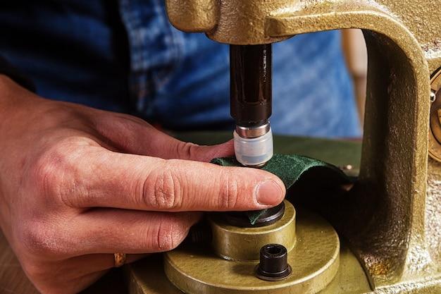Un gros plan d'un fourreur rabats boutons en métal noir sur une ceinture en cuir marron