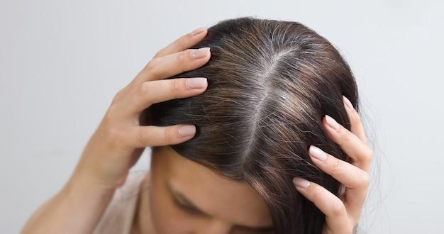 Gros plan, des fragments de cheveux gris sur la tête d'une jeune femme. concept de cheveux gris au début. couleur et structure des cheveux gris
