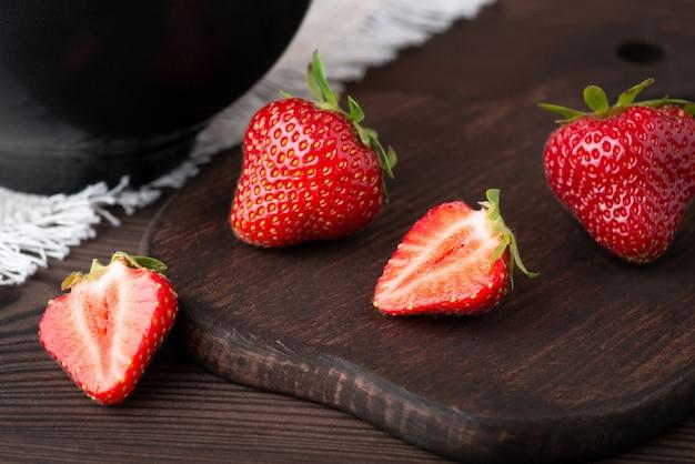 Gros plan d'une fraise coupée en deux sur une planche à découper sombre