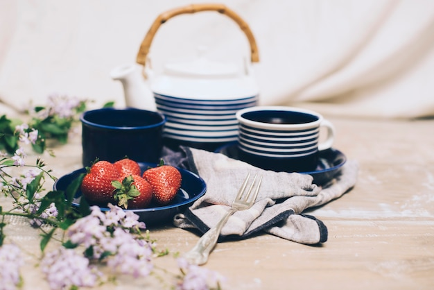 Gros plan, fraise, et, ensemble thé, à, fleurs roses, sur, bois, toile de fond