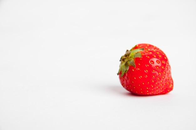 Gros plan d'une fraise rouge sur une surface blanche
