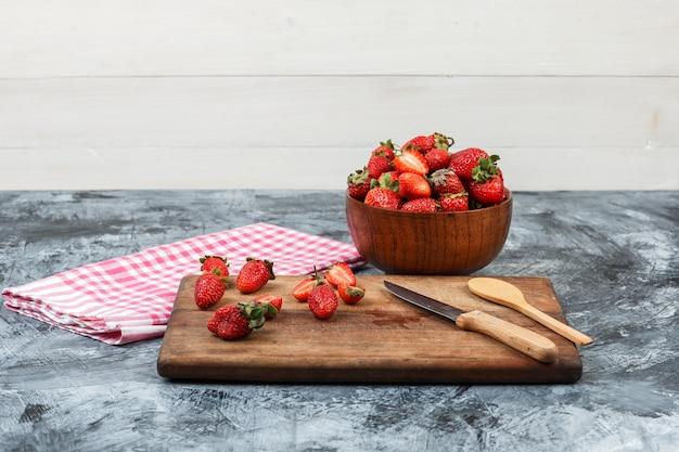 Gros plan des fraises et des ustensiles de cuisine sur une planche à découper en bois avec nappe vichy rouge et un bol de fraises sur marbre bleu foncé et fond en bois blanc. horizontal