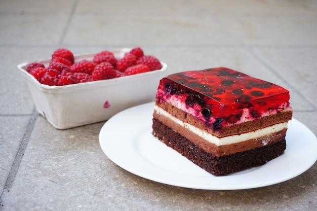 Gros plan de framboises dans un récipient en plastique à côté d'un morceau de gâteau aux framboises