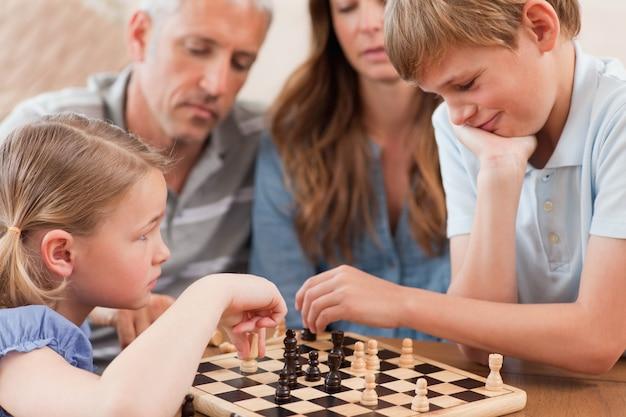Gros plan de frères et sœurs jouant aux échecs devant leurs parents