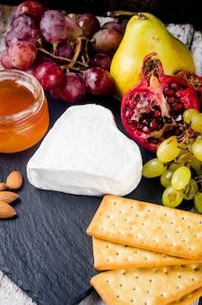 Gros plan de fromage camembert avec du miel, des noix, de la vigne