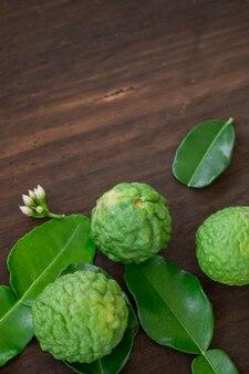 Gros plan de fruits de bergamote sur fond de bois, (chaux de kaffir)