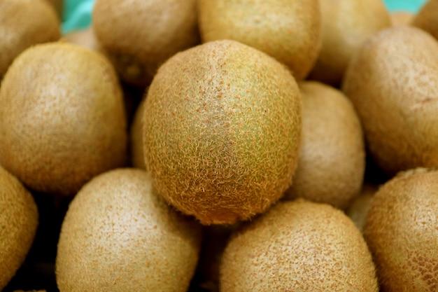 Gros plan de fruits kiwis frais sur une pile de fruits kiwis floue