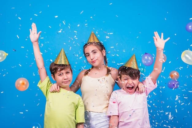 Gros plan, gai, frères soeurs, à, confetti, et, ballons, sur, toile de fond bleu