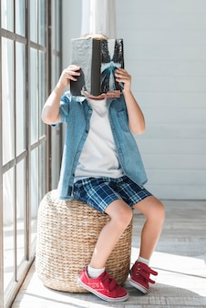 Gros plan d'un garçon assis sur un tabouret en osier près de la fenêtre qui couvre son visage avec un livre