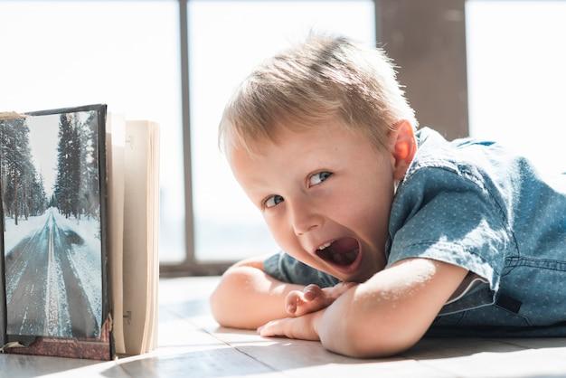 Gros plan, de, garçon, coucher plancher, crier, près, les, livre ouvert