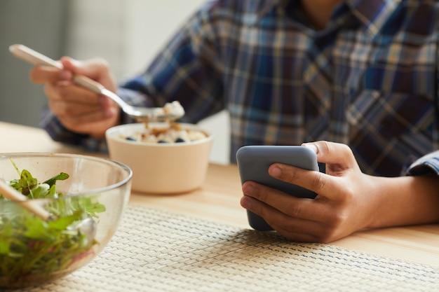 Gros plan d'un garçon mangeant à la table et en utilisant son téléphone portable dans la cuisine