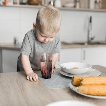 Gros plan d'un garçon mignon blond à la recherche dans le verre de jus