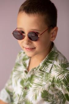 Gros plan garçon posant avec des lunettes de soleil
