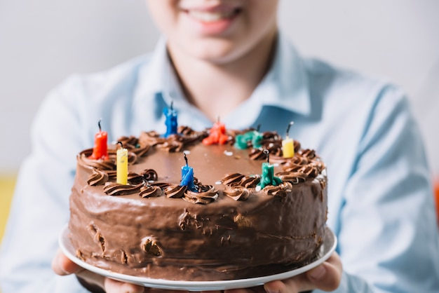 Gros plan d'un garçon souriant montrant un gâteau au chocolat décoré de bougies colorées