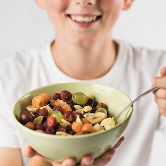 Gros plan d'un garçon souriant, montrant une salade de fruits dans un bol en céramique