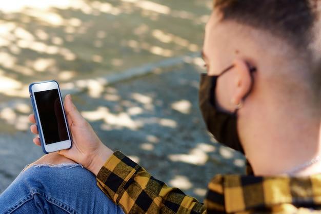 Gros plan d'un gars à l'aide de son smartphone à l'extérieur