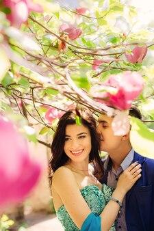 Un gros plan d'un gars qui veut embrasser une femme parmi les branches de magnolia avec des fleurs