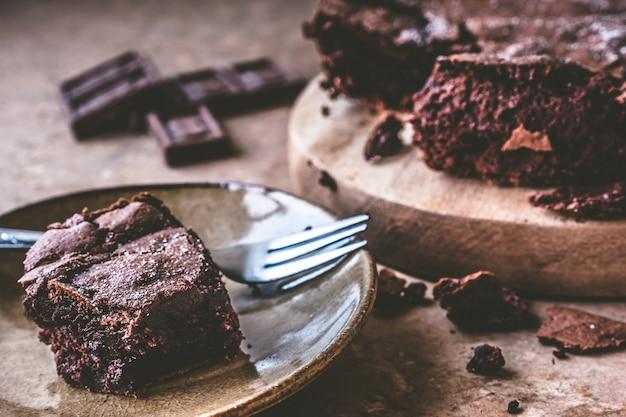 Gros plan de gâteau au chocolat sur un plat avec une fourchette.