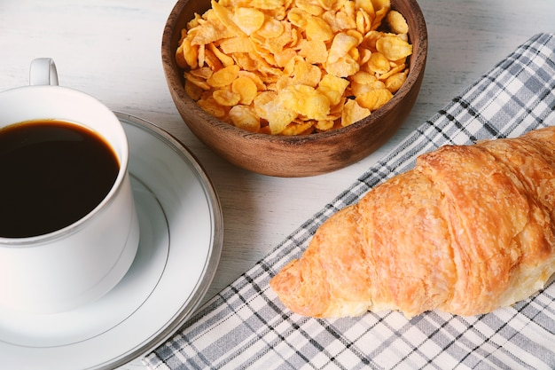 Gros plan de gâteau aux fruits de la passion, pain grillé, café, yaourt, céréales.