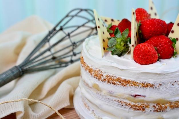 Gros plan sur un gâteau nu avec des fraises et des morceaux de chocolat sur le dessus, dessert sucré
