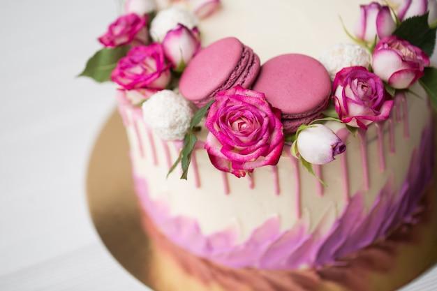Gros plan sur le gâteau avec des roses et des macarons