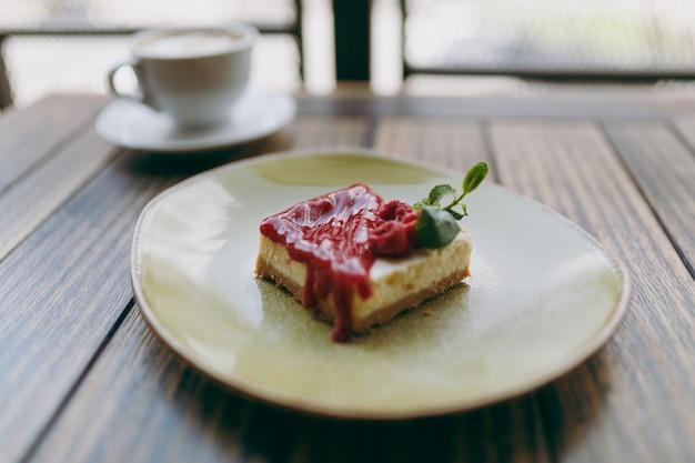 Gros plan de gâteau avec sauce aux framboises sur plaque, tasse de cappuccino allongé sur une table en bois dans un café-restaurant café-restaurant. vue aérienne de dessus. concept de mode de vie. copiez la publicité de l'espace. espace publicitaire