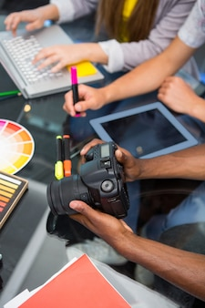 Gros plan des gens d'affaires créatifs avec appareil photo numérique