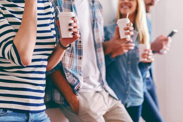 Gros plan de gens d'affaires debout contre le mur en pause et boire du café à emporter.