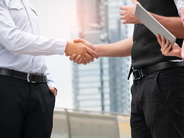Gros plan des gens d'affaires handshaking sur fond de ville. réunion extérieure de partenariat d'affaires