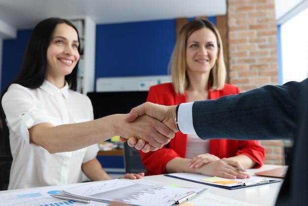 Gros plan de gens d'affaires prospères poignée de main au bureau