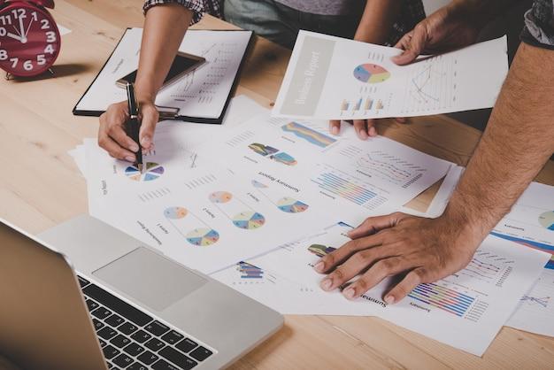 Gros plan des gens d'affaires qui travaillent avec un document commercial lors d'une discussion à la réunion.