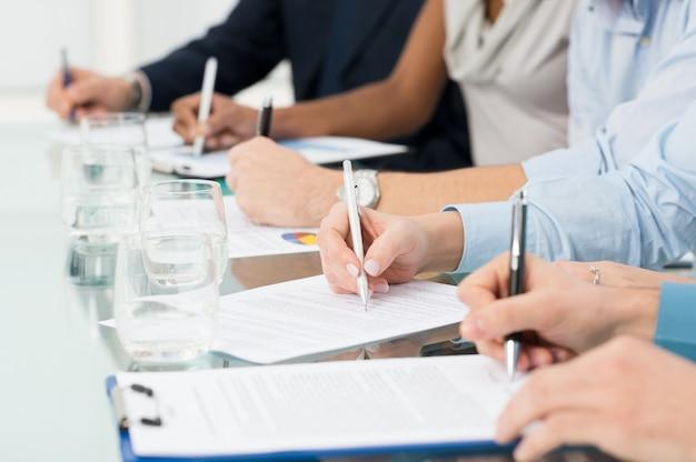 Gros plan des gens d'affaires remettre le papier en prenant des notes au séminaire