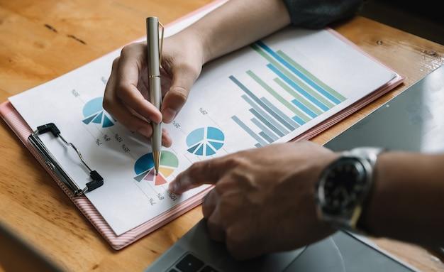 Gros plan des gens d'affaires réunis pour discuter de la situation sur le marché. rapport financier d'entreprise.