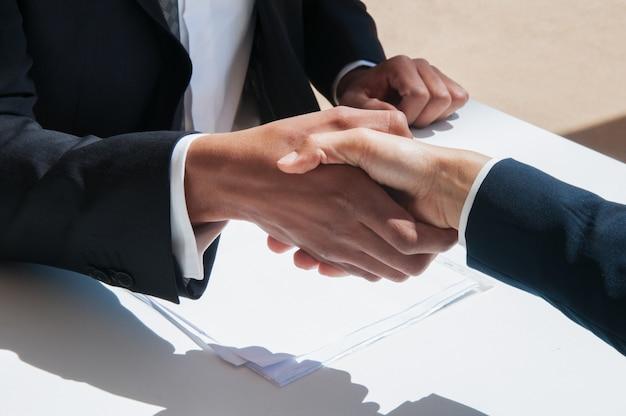 Gros plan de gens d'affaires se serrant la main à l'extérieur