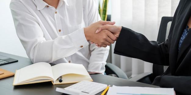 Gros plan sur des gens d'affaires se serrant la main, finissant la réunion, l'étiquette des affaires, les félicitations, le concept de fusion et d'acquisition