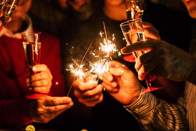 Gros plan sur des gens célèbrent le nouvel an avec des cierges magiques et du vin mousseux - concept de vie nocturne - anniversaire ou amis de fête s'amusant ensemble