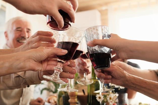 Gros plan de gens heureux, grillage avec des verres de vin rouge pendant le dîner de vacances