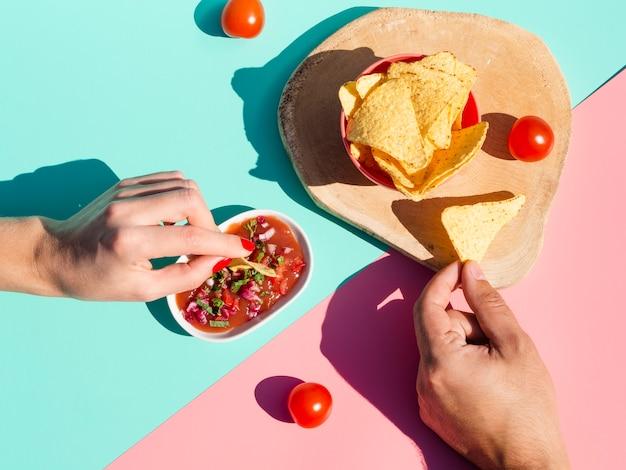 Gros plan des gens avec de la sauce et des chips de tortilla