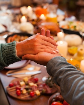 Gros plan des gens se tenant la main au dîner
